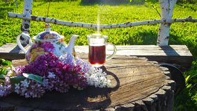 A Cup of tea on a wooden table. A Cup of tea on a wooden table and a bouquet of beautiful lilacs Royalty Free Stock Photos