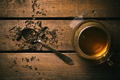 Cup of tea on a wooden table. A glass cup of tea on the wooden desk with a spoon and some dried leaves stock photography
