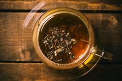 Cup of tea on a wooden table. A glass cup of tea on the wooden desk with a spoon and some dried leaves royalty free stock images