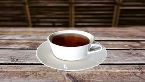 A cup of tea on a wooden table. A cup of tea lies on a wooden table in an elegant and natural landscape stock footage