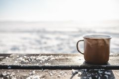 Cup of tea on the wooden table outdoors. Cup of tea on the brown wooden table outdoors. Beautiful sunlight and snow on the background stock photo
