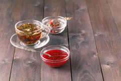 Cup of tea on wooden table over wooden background with raspberry. Jam Stock Photos