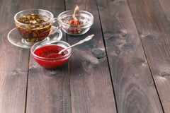 Cup of tea on wooden table over wooden background with raspberry. Jam Stock Image