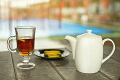 Cup of tea on the wooden table. At the pool Stock Photography