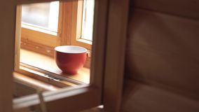Cup of tea on a wooden window sill. Cup of tea on a wooden windowsill. Brake time with a mug of coffee and city view. Though window. mug of tea on a wooden stock footage