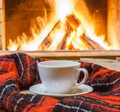 A cup of  tea,  woolen things near cozy fireplace. Royalty Free Stock Images