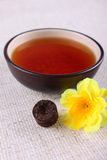 Cup of tea with yellow flower on linen napkin Royalty Free Stock Image