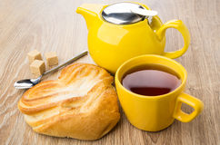 Cup of tea, yellow teapot, spoon and bun with sugar Stock Images