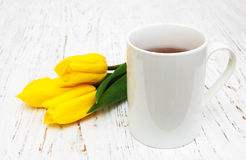 Cup of tea and yellow tulips Stock Photo