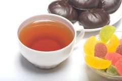 Cup with tea, a zephyr and fruit candy. Royalty Free Stock Images