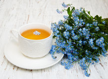 Cup of teand forget me not flowers Stock Photos