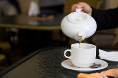Cup and teapot in cafe Stock Images