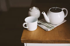 Cup, teapot on kitchen table. White cup, teapot and spoon on wooden kitchen table Stock Photo