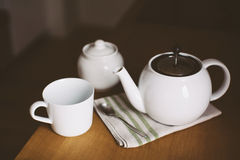 Cup, teapot on kitchen table. White cup, teapot and spoon on wooden kitchen table Royalty Free Stock Photography