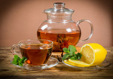Cup and teapot of tea with mint leaf and lemon Royalty Free Stock Images