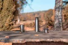 A cup of tee standing on a outdoor desk in a beautidul autumn scenery. coffee, tee, fall, landscape, cup, outdoor drink; stock photography