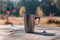 A cup of tee standing on a outdoor desk in a beautidul autumn scenery. coffee, tee, fall, landscape, cup, outdoor drink; stock photos