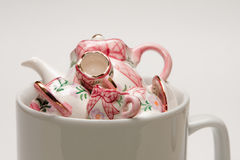 Cup of thee. A mug filled with miniature pieces of a tea set Stock Images