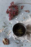 Cup of thyme infusion on table with red berries branch Stock Photo