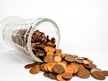 Cup tipped over with coins spilling out royalty free stock images