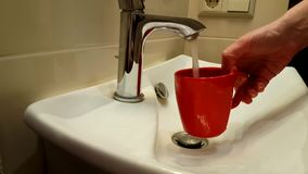 Cup to draw water from a tap. Pouringn stock video
