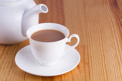 Cup of traditional English Tea with white china teapot Royalty Free Stock Image