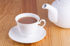 Cup of traditional English Tea with white china teapot Royalty Free Stock Photo