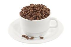 Cup und Saucer voll der Kaffeebohnen, Seitenansicht stockbilder