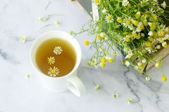 A cup of useful soothing chamomile tea, a bouquet of daisies and books on a marble table. Selective focus royalty free stock image