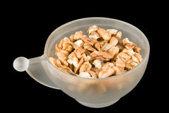 Cup of walnuts. Walnuts isolated on black background in white cup royalty free stock photography