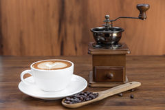 Cup of warm coffee and coffee grinder Royalty Free Stock Photography