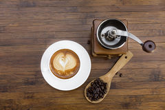Cup of warm coffee and coffee grinder Stock Image