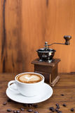 Cup of warm coffee and coffee grinder Stock Photos