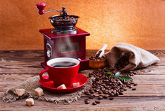 Cup of warm coffee and grinder. Royalty Free Stock Image