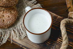Cup of warm milk and bread on a wooden background. Cup of warm milk and bread on a old wooden tray Stock Photo