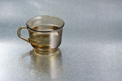 Cup with water. On silver background Royalty Free Stock Photography