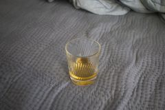 A cup of whisky on the bed.  royalty free stock images