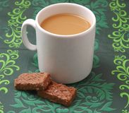 A cup of white coffee and black cakes Royalty Free Stock Photos
