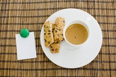 A cup of white coffee and chocolate chip cookies with notepad an Royalty Free Stock Image