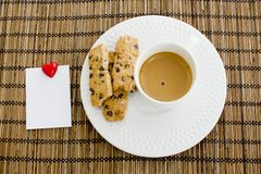 A cup of white coffee and chocolate chip cookies with notepad an Stock Image