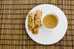 A cup of white coffee and chocolate chip cookies over a wooden t Stock Images