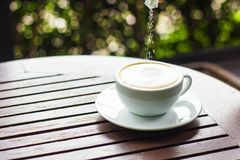 A cup of white coffee is placed on a brown wooden table and is p. Ut into sugar Royalty Free Stock Images