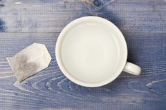 Cup or white mug with transparent hot water and bag of tea. Tea time concept. Mug filled with boiling water and teabag. On blue wooden background. Process of royalty free stock images