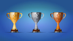 Cup of winners award for first, second and third. Winners position on a blue background Royalty Free Stock Photo