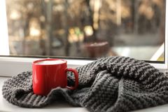 Cup of winter drink and knitted scarf on windowsill. Space for text stock image
