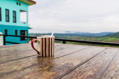 Cup on a wooden table. Image of a cup on a wooden table Stock Photos