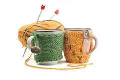 Cup in woolen garments. Cup in knitted covers with a ball of yarn and knitting Stock Photo