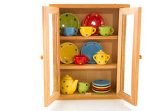 Cupboard with cheerful crockery stock image