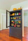 Cupboard with Colorful Dinnerware in Home. Cupboard with colorful stoneware dinnerware in home with cherry hardwood floor stock photo