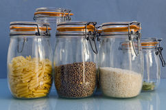 In the Cupboard. Cupboard containing jars filled with pasta, lentils and rice Royalty Free Stock Images